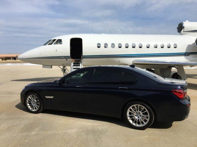 car next to luxury jet
